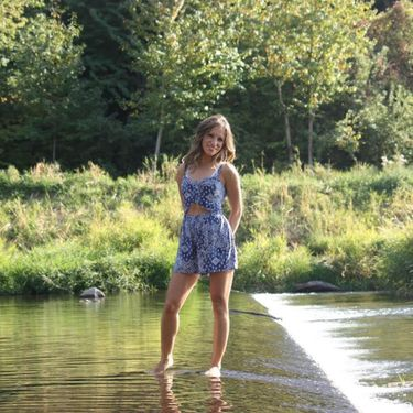 Beautiful Adventist single girl standing in a stream of water